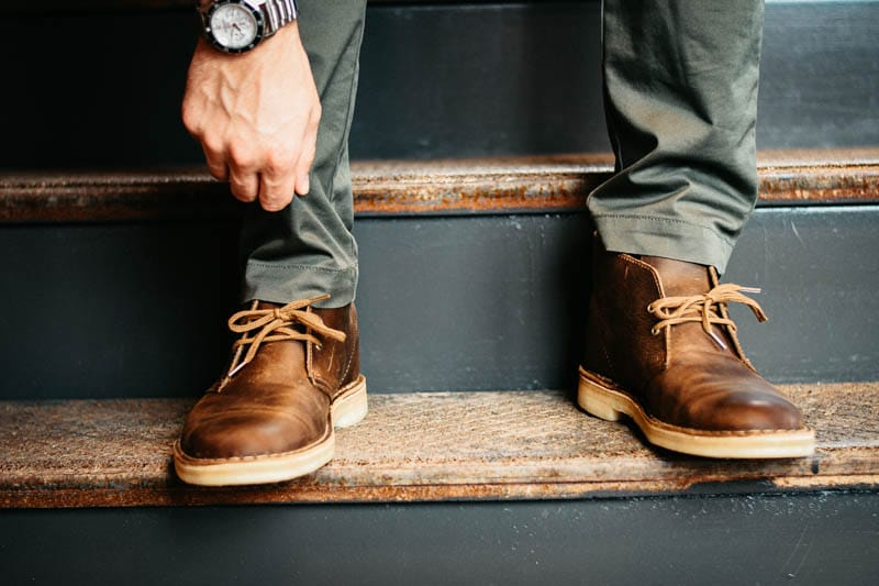 Model on staircase wearing watch and reaching down to touch Clarks Desert boots