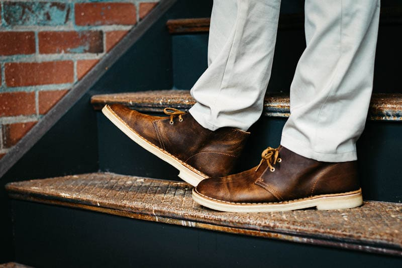 Model wearing Clarks Desert Boots and lifting one boot on stairs