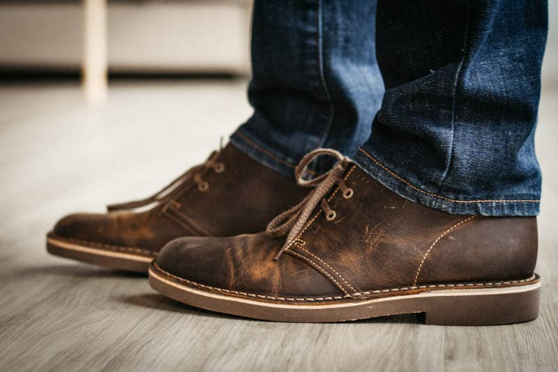 Model wearing Clarks Bushacre with jeans on hardwood floor