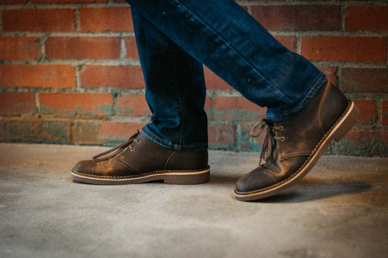 model standing in front of brick wall wearing clarks bushacre 2 desert boots