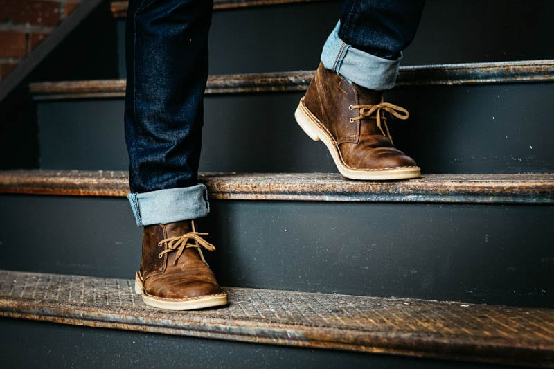 model standing on staircase wearing clarks desert boot with cuffed jeans