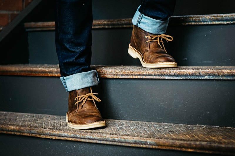 model standing on staircase wearing clarks desert boot