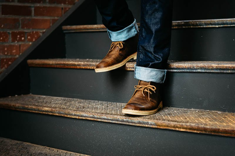 model walking down stairs wearing clarks leather desert boot chukka