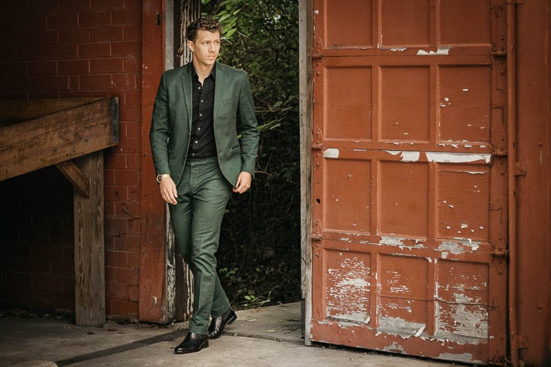 Chelsea boots outfit with green suit black shirt and black chelsea boots