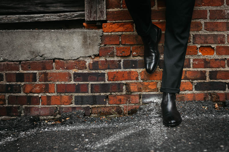 closeup of ace marks troy chelsea boots against brick wall