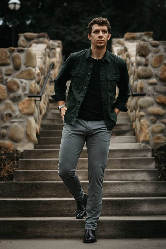 model wearing grey chinos and black ace marks troy chelsea boots with green shirt