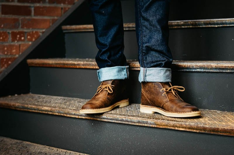 model standing on staircase wearing beeswax color clarks desert boot leather chukka