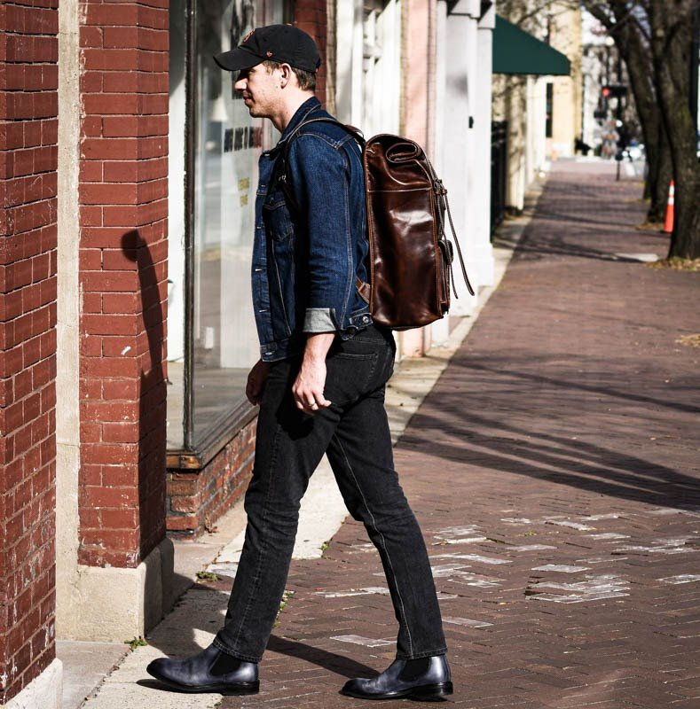 model wearing leather rolltop backpack moral code entering building