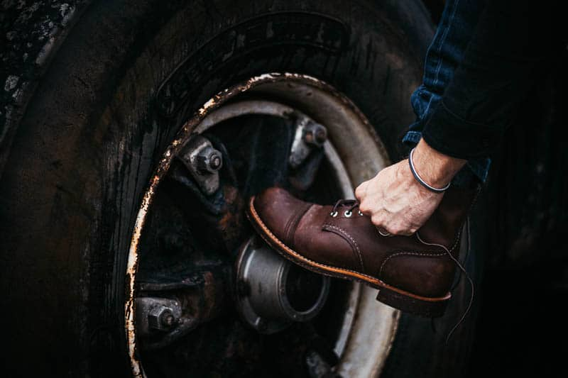 lacing up red wing iron ranger against rusty tire