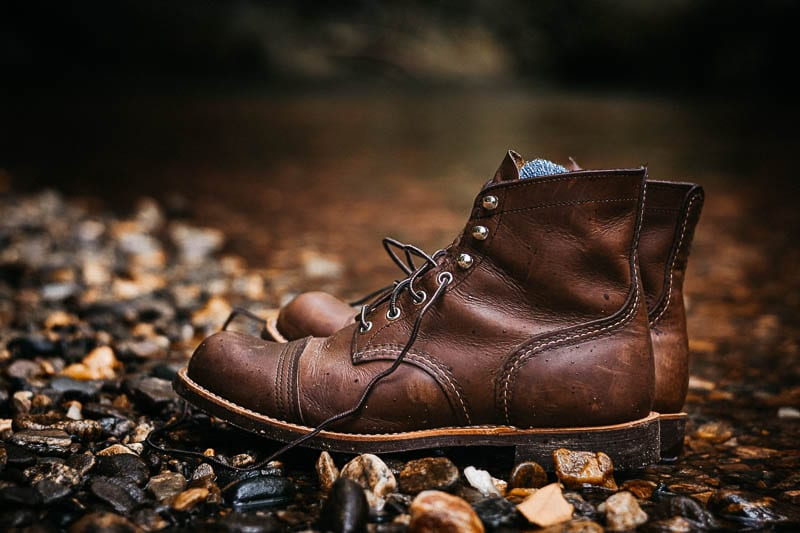 red wing iron ranger boots on gravel next to river