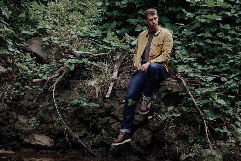 model sitting on brick wall wearing Danner Bull Run boots